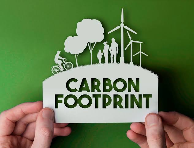 Human Hand Holding A Note Which Representing The Carbon Footprint Concept.
